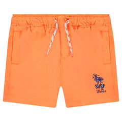 Plain-colored swim trunks with printed palm trees