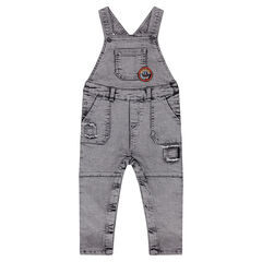 Faded and distressed denim overalls with emblem-shaped badge